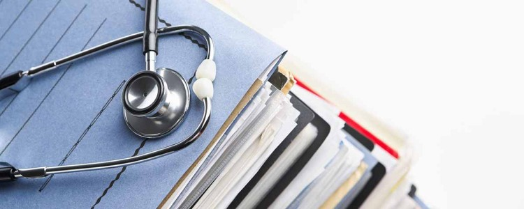 a stack file folders with a stethoscope on top