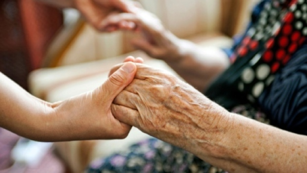A younger persons hands joined with an elderly persons hands