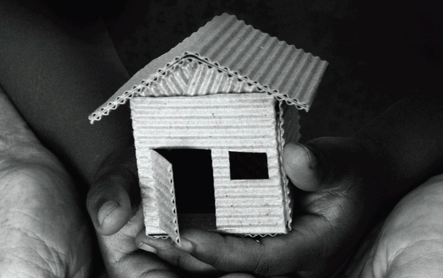 Hands holding a model house made or cardboard