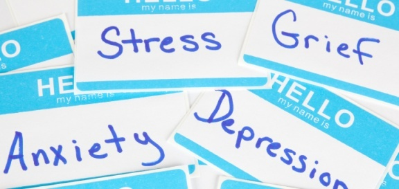 name tag labels in a pile with different mental health disorders written on them,like anxiety, depression, stress