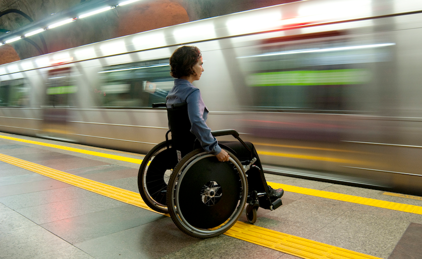 Woman in a wheelchair waiting for the subway