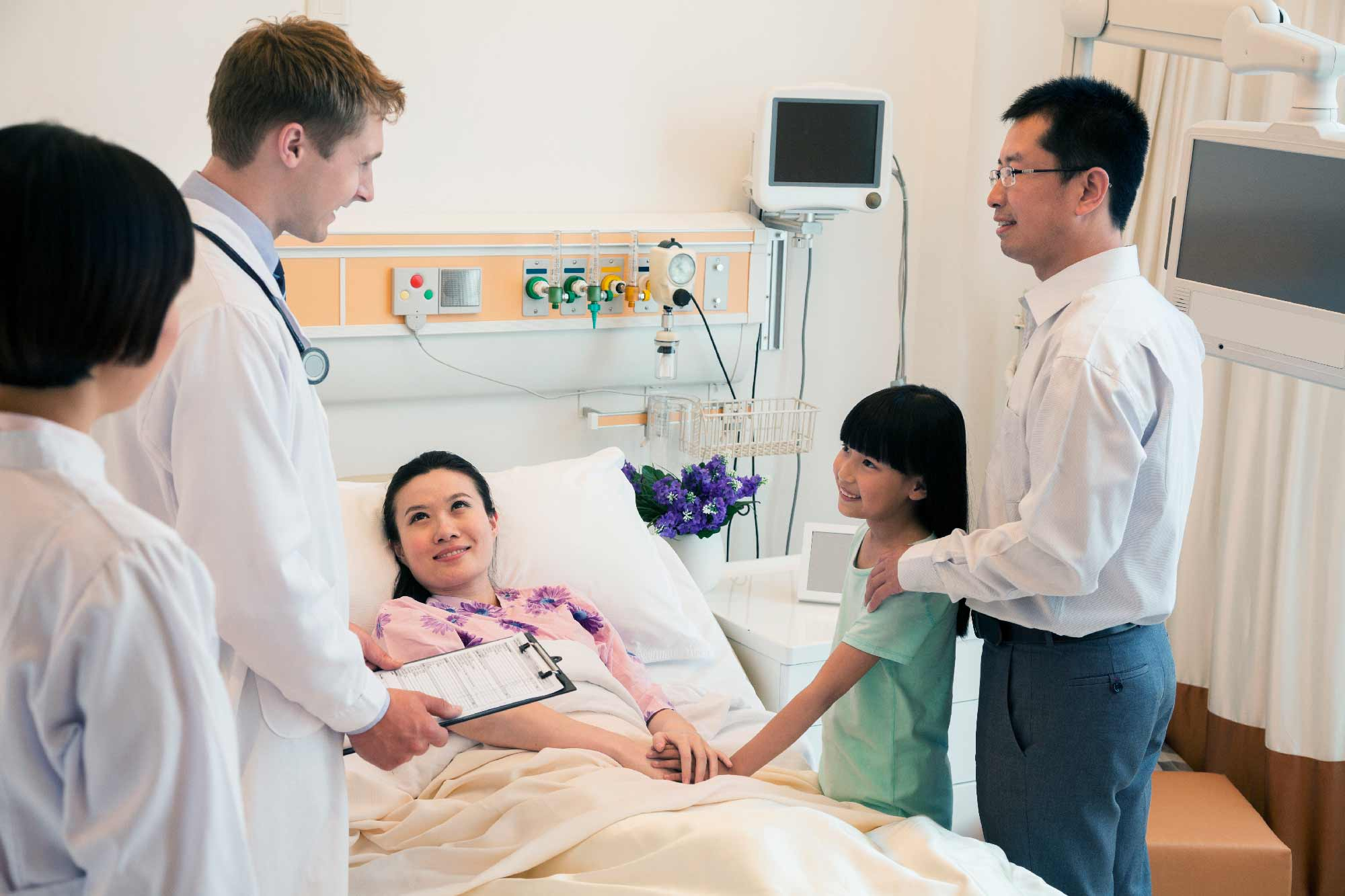 Medical professionals and family members around a person in a hospital bed