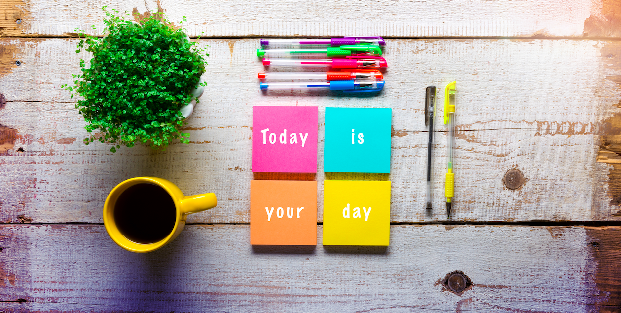 "Wooden desktop with sticky notes that read ""Today is your day"""