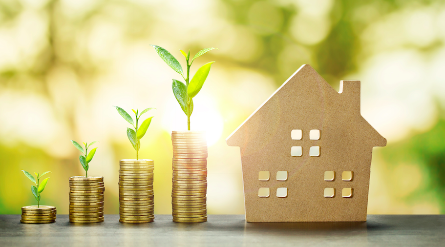 Housing investing concept with gold coins growing sprouts and a cut out house