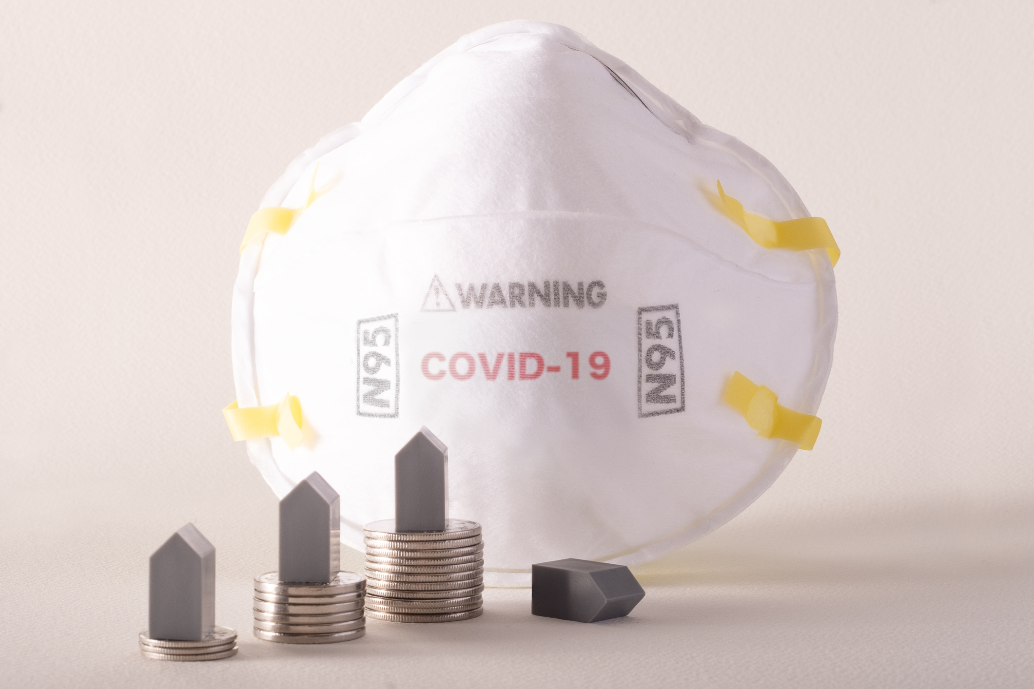 N-95 COVID-19 Face Mask and piles of coins