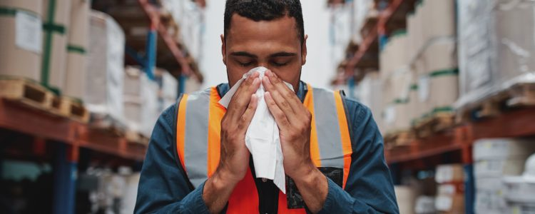 Warehouse worker blowing nose while working wearing safety vest